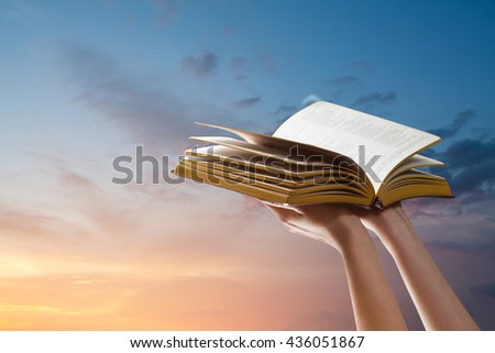 Hands holding Bible over sunset sky