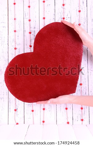 Hands holding big red heart on wooden background - stock photo