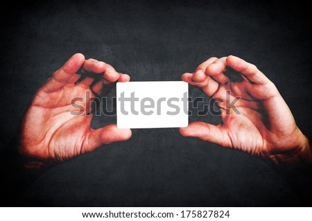 Hands holding blank calling card ion black background  - stock photo