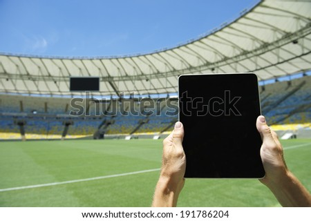 Hands holding blank tablet computer in front of soccer field at football stadium Rio de Janeiro Brazil - stock photo