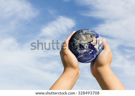 hands holding blue earth on cloud and sky.Elements of this image furnished by NASA