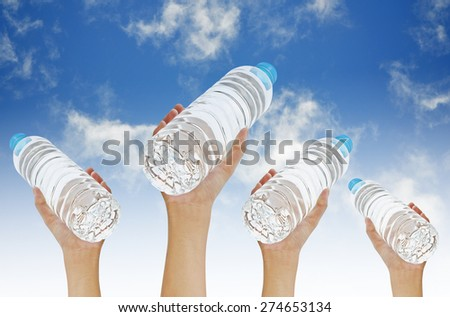 Hands holding bottle water on blue sky background - stock photo