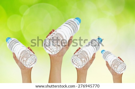 Hands holding bottle water on green bokeh background - stock photo