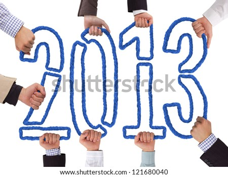 Hands holding bricks forming year 2013 - stock photo