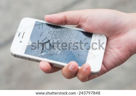 Hands holding broken mobile smartphone - stock photo