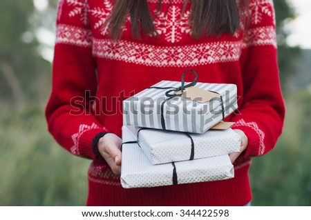 Hands holding Christmas gift. Background with christmas outfit - stock photo