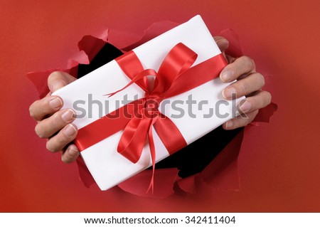 Hands holding Christmas or birthday present breaking through a red torn paper background. - stock photo