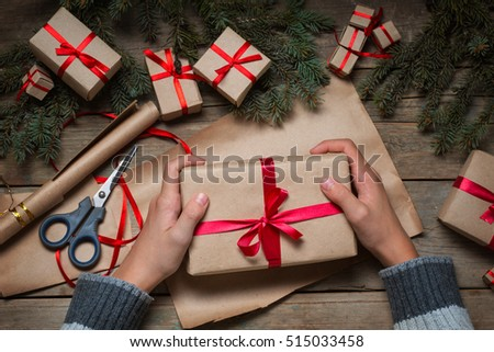 Hands holding Christmas present on the table