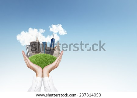 hands holding city on green grass hill - stock photo
