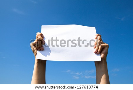 Hands holding clean white sheet paper over the sky - stock photo