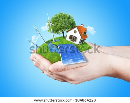 Hands holding clear green meadow with sun battery block, wind mill turbines and countryside house. Concept for ecology, alternative energy, freshness, freedom. Green fields collection. - stock photo