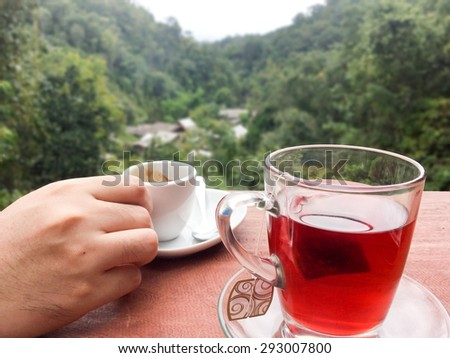 Hands holding coffee cups Resting on a glass of tea on the terrace with mountain views behind. Mae Kum Pong , Chiang Mai , Thailand - stock photo