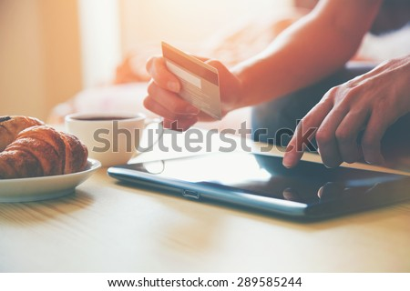 Hands holding credit card and using digital tablet pc with morning coffee and croissant. Online shopping. - stock photo