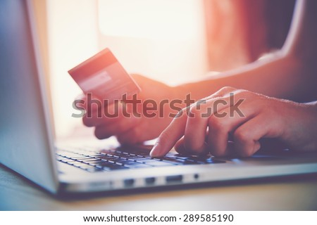 Hands holding credit card and using laptop. Online shopping - stock photo