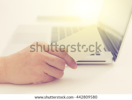 Hands holding credit card and using laptop. Online shopping,credit card content,credit card background.