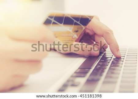Hands holding credit card and using laptop. Online shopping,credit card content,credit card background. - stock photo