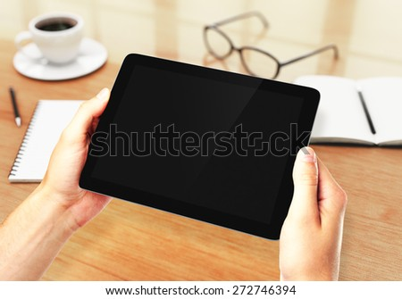 Hands holding digital tablet in the workplace - stock photo