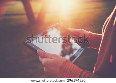 hands holding digital tablet pc in summer sunset light - stock photo