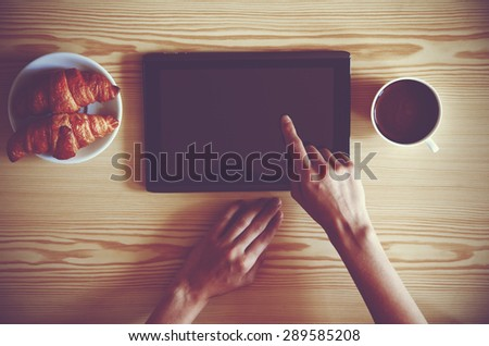 Hands holding digital tablet pc with morning coffee and croissant. View from above - stock photo