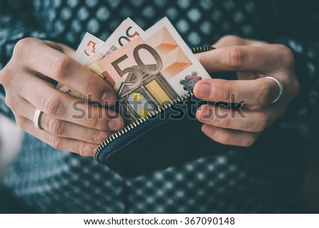 Hands holding euro bills and small money pouch. Toned picture - stock photo