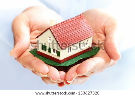 Hands holding Family house model. Real estate background.