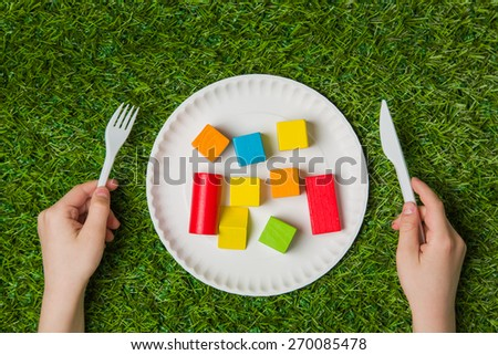 Hands holding fork and knife  over construction color wooden blocks with green grass background close up