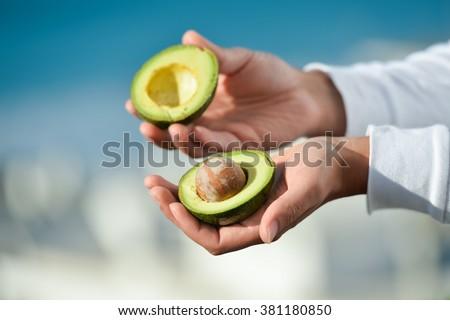 Hands holding fresh avocado cut in half on sun light blue sky background. Closeup  - stock photo
