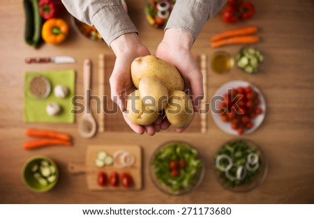 Hands holding fresh harvested potatoes with raw colorful seasonal vegetables on background, top view - stock photo
