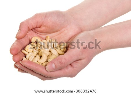 Hands holding fresh roasted cashew nuts on white background - stock photo