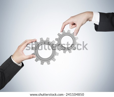 hands holding gears on a blue background - stock photo