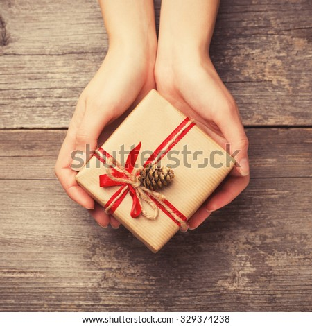 Hands holding gift box with pine cone - stock photo