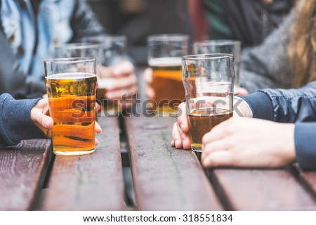 Hands holding glasses with beer on a table at pub in London. A group of friends is enjoying beer time in the city, close up on the glasses. - stock photo