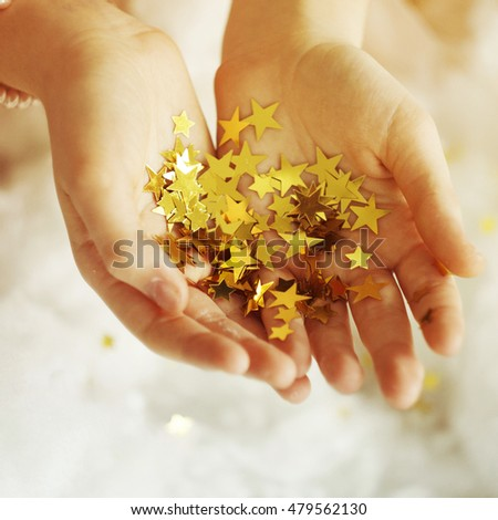 Hands holding golden tinsel stars