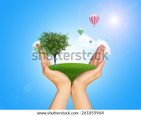 Hands holding green grass with ground. Standing tree and flying hot air balloon in background. Blue isolated - stock photo