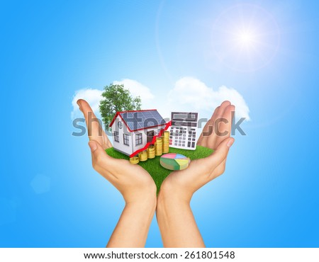 Hands holding green grass with house on ground. Standing tree and clouds in background. Blue isolated - stock photo