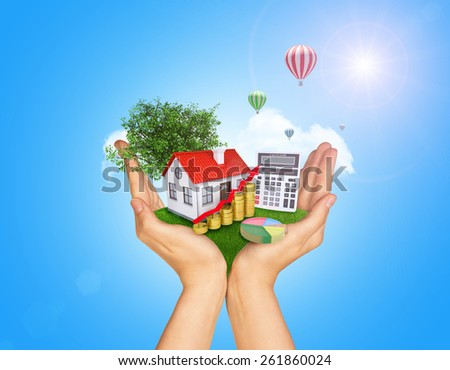 Hands holding green grass with house on ground. Standing tree and flying hot air balloon in background. Blue isolated - stock photo