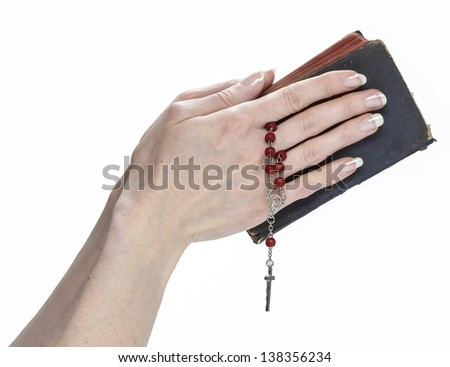 Hands holding Holy Bible and red rosary isolated on white background. - stock photo