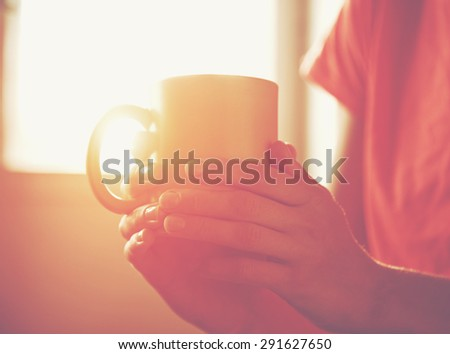 hands holding hot cup of tea or coffee in morning sunlight - stock photo