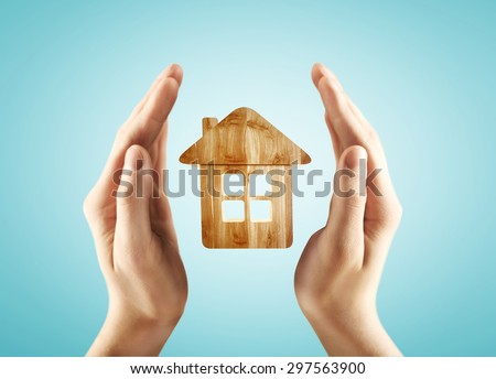 hands holding house on a blue background - stock photo