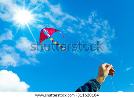 Hands holding kite in the cloudy sky. Focus to the hand