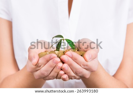 Hands holding little plant growing from coins as symbol of money saving and growth or investment - stock photo