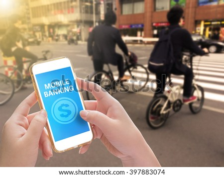 Hands holding mobile phone with Mobile banking on screen with blurred man ride a bike - stock photo