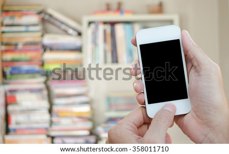 Hands holding mobile smart phone with blurred background of books on shelf and stack at library, education concept. - stock photo