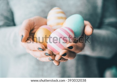 Hands holding modern painted easter eggs. Selective focus. Toned picture - stock photo