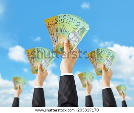 Hands holding money - Australian dollar (AUD) banknotes - money raising, funding & consumerism concept - stock photo