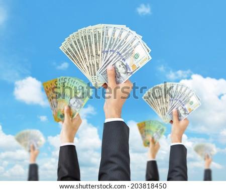 Hands holding money in multi currencies - money raising, funding & consumerism concept - stock photo