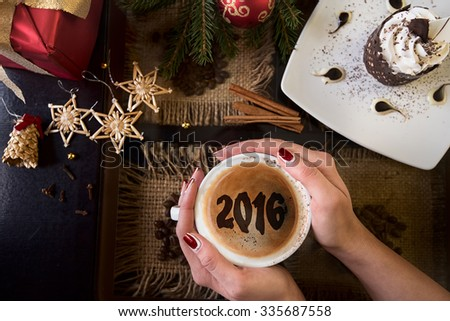 Hands holding mug of coffee close-up, on new year background - stock photo