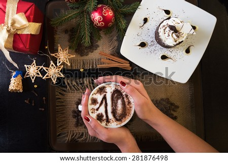 Hands holding mug of coffee with ten signs, close-up, on new year background - stock photo