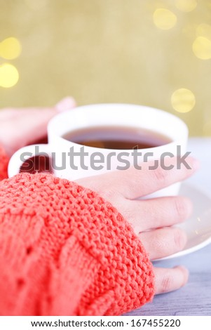 Hands holding mug of hot drink, close-up, on bright background - stock photo