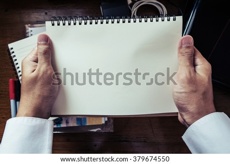 hands holding notebook - stock photo